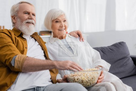 Smiling senior couple holding bowl with popcorn on blurred foreground