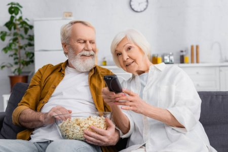 Senior woman clicking channels near husband with bowl of popcorn on couch