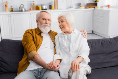 Senior couple hugging and holding hands on couch