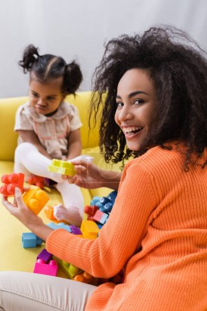 happy african american mother playing building blocks with offended toddler kid on blurred background