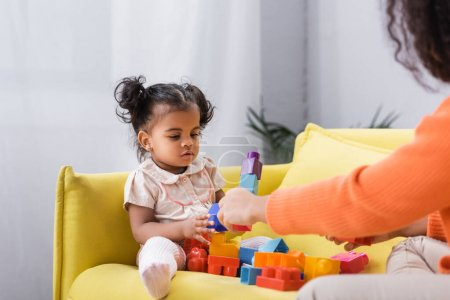 african american toddler girl sitting on sofa and playing building blocks with mother on blurred foreground