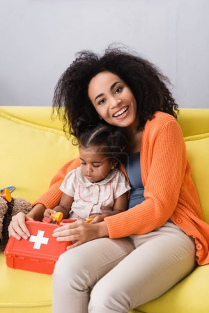 Photo for Smiling african american mother sitting with toddler daughter and holding toy first aid kit in living room - Royalty Free Image