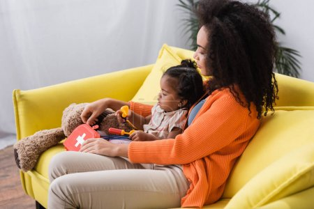 Photo for African american mother sitting with toddler daughter and holding toy first aid kit in living room - Royalty Free Image