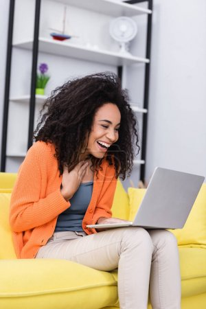 Photo for Happy african american freelancer laughing while using laptop at home - Royalty Free Image