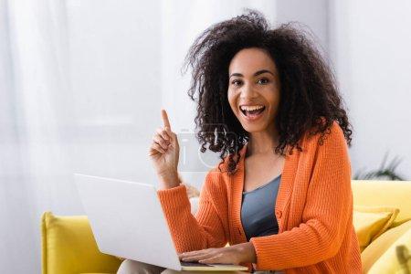 Photo pour Excité afro-américain pigiste pointant avec le doigt près d'un ordinateur portable à la maison - image libre de droit