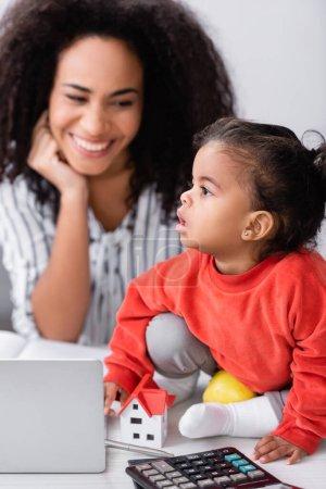 Photo pour Tout-petit fille assis sur le bureau près heureuse mère afro-américaine sur fond flou - image libre de droit