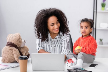 Photo for Happy african american mother looking at toddler daughter sitting on desk with apple near gadgets - Royalty Free Image