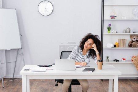 femme afro-américaine coûteuse écrit dans un cahier près de gadgets sur le bureau