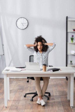 Foto de Estresado freelancer afroamericano mirando a la computadora portátil mientras trabaja desde casa - Imagen libre de derechos