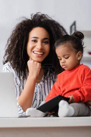 Photo pour Souriant afro-américaine mère regardant caméra près de tout-petit fille sur le bureau - image libre de droit