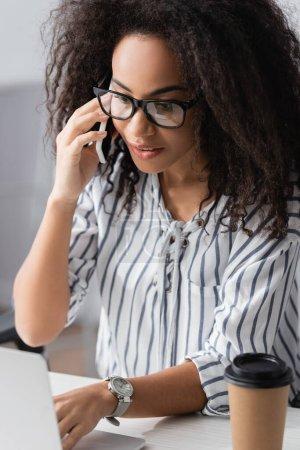 freelancer afroamericano en gafas hablando en smartphone cerca de laptop en casa