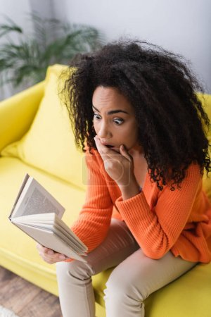 shocked african american woman reading book while sitting on couch