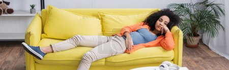 bored african american woman chilling on yellow couch, banner
