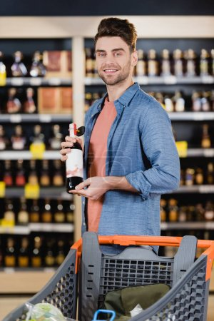 Young man smiling at camera while holding bottle of wine near shopping trolley in supermarket