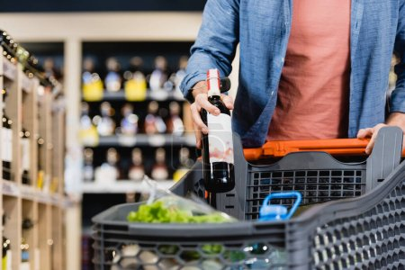 Cropped view of man putting bottle of wine in shopping cart on blurred foreground