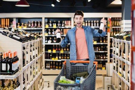 Amazed man holding bottles of wine near shopping cart on blurred foreground in supermarket