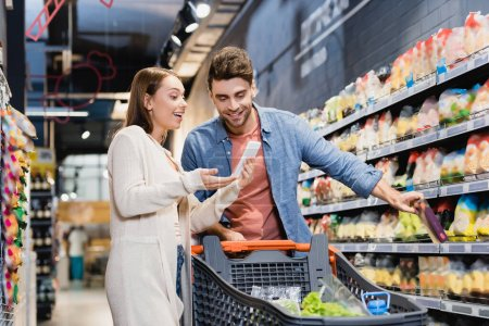 Photo for Smiling woman pointing at smartphone near boyfriend and shopping cart in supermarket - Royalty Free Image
