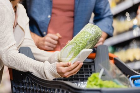 Cropped view of woman holding lettuce and smartphone near boyfriend on blurred background in supermarket
