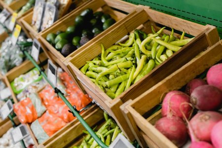 Photo for Fresh peppers on counter in supermarket on blurred background - Royalty Free Image
