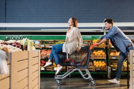 Cheerful couple rolling on shopping cart near groceries in supermarket