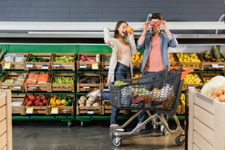 Cheerful couple holding fruits near faces and shopping cart in supermarket