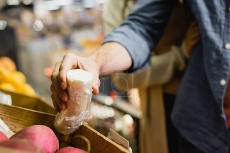 Photo for Cropped view of man holding radish near girlfriend on blurred background in supermarket - Royalty Free Image