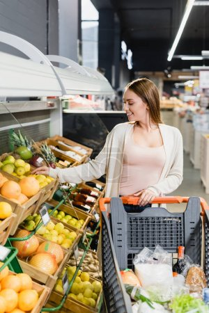 Cheerful woman taking grapefruit near fruits and shopping cart in supermarket