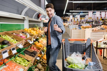 Cheerful man pointing with fingers at camera near shopping trolley and food in supermarket