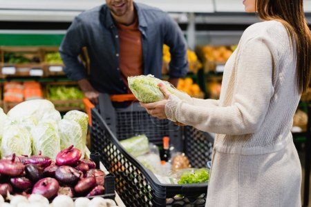 Cropped view of woman holding lettuce near vegetables and boyfriend with shopping cart in supermarket