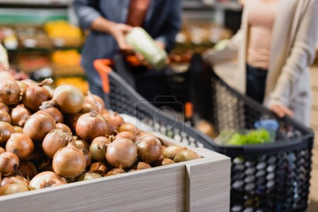 Photo for Cropped view of onions near couple on blurred background in supermarket - Royalty Free Image