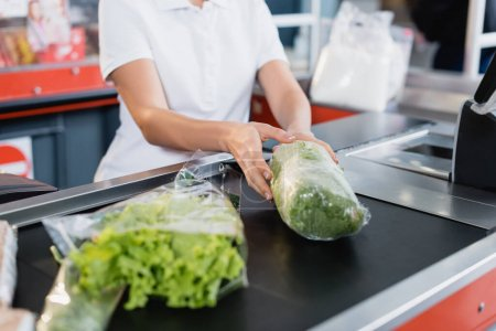 Photo for Cropped view of cashier taking lettuce from supermarket checkout - Royalty Free Image