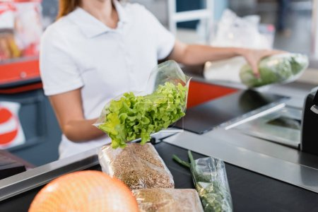 Photo for Cropped view of lettuce in hand of cashier in supermarket on blurred background - Royalty Free Image