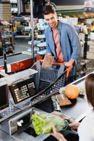 Smiling man holding package with buckwheat near cashier on supermarket checkout