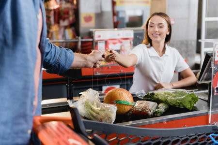 Man giving credit card to smiling cashier near food on supermarket checkout