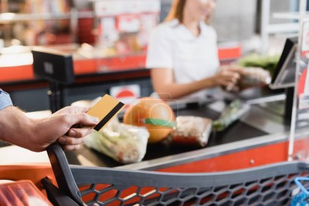 Cropped view of man holding credit card near shopping cart and supermarket checkout on blurred background