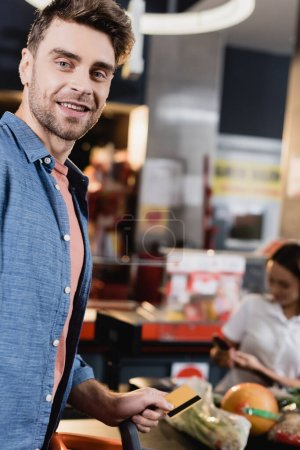 Smiling customer holding credit card near supermarket checkout on blurred background