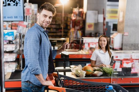 Smiling man holding credit card near shopping cart and supermarket checkout on blurred background