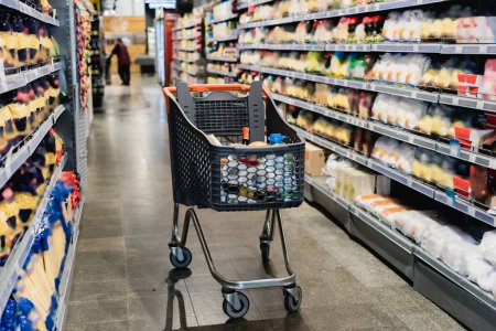 Shopping trolley near shelves with groceries in supermarket