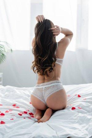Photo pour Vue arrière de jeune femme sexy en sous-vêtements blancs assis sur le lit avec des coeurs de papier rouge - image libre de droit