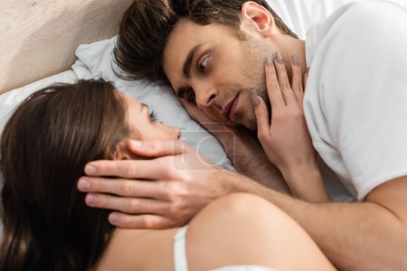 top view of man and woman lying in bed and looking at each other