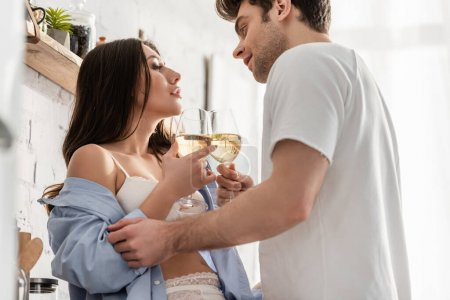 Photo for Side view of sexy couple holding glasses with wine and looking at each other - Royalty Free Image