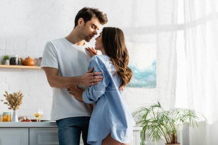 Photo pour Homme étreignant femme sensuelle en chemise bleue dans la cuisine - image libre de droit