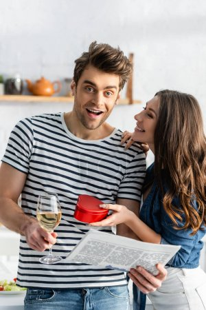 amazed man holding glass of wine and newspaper near cheerful girlfriend with heart-shaped gift box