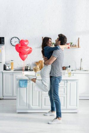 Photo pour Toute la longueur du couple embrassant près de ballons en forme de coeur dans la cuisine moderne - image libre de droit