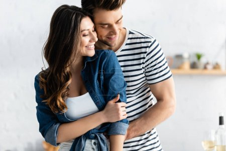 Photo for Happy man embracing joyful girlfriend and smiling in kitchen - Royalty Free Image