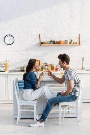Photo pour Vue latérale de couple heureux cliquetis verres avec du vin dans la cuisine - image libre de droit