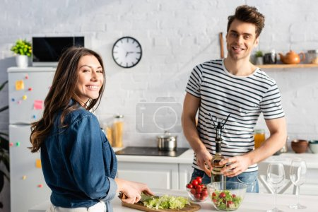 Photo for Cheerful woman looking at camera while cutting lettuce near boyfriend opening bottle of wine on blurred background - Royalty Free Image
