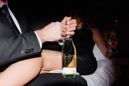 Photo for Man opening bottle of champagne near girlfriend on bed on blurred background in hotel during night - Royalty Free Image