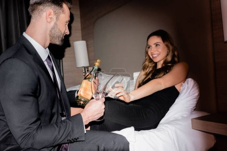 Photo for Smiling woman in dress holding glass near boyfriend in suit with bottle of champagne in hotel during night - Royalty Free Image