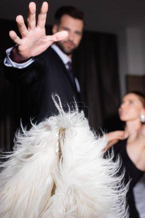 Photo pour Homme en costume jetant veste moelleuse près de petite amie sur fond flou à l'hôtel - image libre de droit